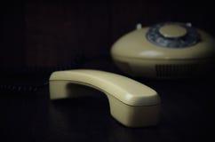 Microtelefono e telefono antiquati su un fondo di legno scuro Hotepibtawy immagine stock