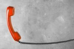 Microtelefono rosso dal telefono della linea terrestre sulla parete del fondo fotografia stock libera da diritti