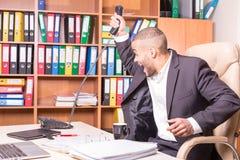 Microtelefono throing dell'uomo africano dopo la chiamata sgradevole immagine stock libera da diritti