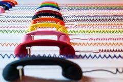 Microteléfonos multicolores con el alambre espiral en un fondo blanco Fotografía de archivo libre de regalías