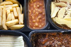 Microwavable ready to cook, frozen foods, in plastic boxes . Selection of frozen, processed, ready made foods, consisting of potato chips, mince, lasagna in royalty free stock images