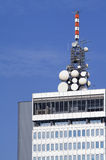 Microwave antennae on building top. Cluster of different microwave antennae on top of a high rise modern office building stock photos