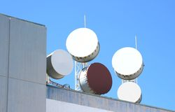Microwave antennas on rooftop. Large circular communications antenna on the rooftop of a commercial building Royalty Free Stock Photography