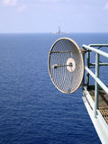 Microwave Communications Anten. A Microwave communications Antenna is bolted to a handrail and provides communication from an offshore platform back to the land Royalty Free Stock Photography