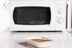 Microwave oven with frozen food. Microwave oven with portion of frozen food Stock Image