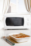 Microwave oven with frozen food. Microwave oven with portion of frozen food Royalty Free Stock Images