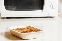 Microwave oven with frozen food. Microwave oven with portion of frozen food Royalty Free Stock Image