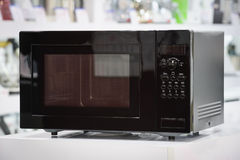 Microwave oven in retail store. Single black microwave oven at retail store shelf, defocused background stock images