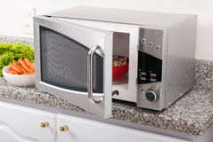 Microwave oven. Silver microwave oven on the kitchen counter Royalty Free Stock Photo
