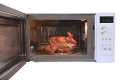 The microwave oven is warm roasted chicken with black pepper. Stock Photos