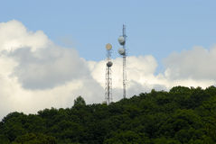 Microwave Towers and Cumulus Clouds. Dual microwave communications towers with cumulus clouds building in a deep blue sky Royalty Free Stock Photos