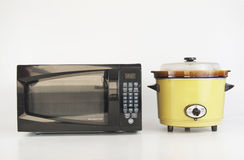 Microwave Versus Slow Cooker. Microwave sitting side by side with a slow cooker to compare instant with taking time. Fast versus slow royalty free stock photography