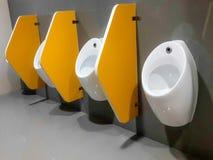 Mictórios brancos do close up no men& x27; banheiro de s Imagens de Stock