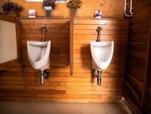 Mictórios brancos na parede de madeira da teca, sala do banho imagens de stock royalty free