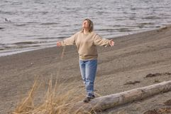 Mid 40's Woman Celebrating Life. This mid 40's aged blond woman is celebrating life at a moment at the beach walking on a log.  There's an expression of Royalty Free Stock Images