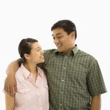 Mid adult Asian couple. Mid adult Asian couple standing with arms around eachother and smiling at one another royalty free stock photo