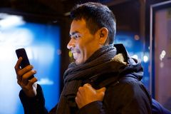 Mid adult asian man using cell phone. Close up side portrait of smiling mid adult asian man looking at his cell phone outdoors in night Stock Photography