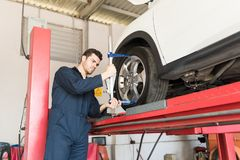 Automobile Worker Using Camber Caster Adapter On Tire. Mid adult automobile worker using camber caster adapter on tire in garage stock photo