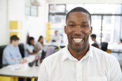 Mid adult black man smiling to camera in an open plan office Royalty Free Stock Photos