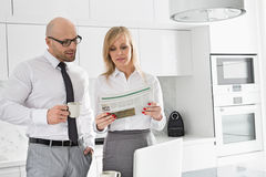 Mid adult business couple reading newspaper while having coffee in kitchen Stock Photography