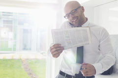 Mid adult businessman on call while holding newspaper and coffee cup at home Royalty Free Stock Photo