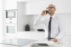 Mid adult businessman on call at kitchen counter Stock Image
