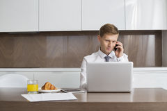 Mid adult businessman on call while using laptop at breakfast table Stock Images