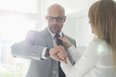 Mid adult businessman checking wristwatch while woman adjusting his tie at home. Mid adult businessman checking wristwatch while women adjusting his tie at home Royalty Free Stock Photography