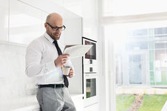 Mid adult businessman having coffee while reading newspaper at home Royalty Free Stock Images