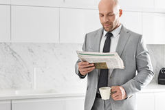 Mid adult businessman having coffee while reading newspaper in kitchen Stock Photography