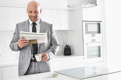 Mid adult businessman having coffee while reading newspaper in kitchen Stock Photo