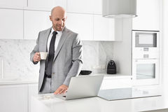 Mid adult businessman having coffee while using laptop in kitchen Stock Images