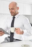 Mid adult businessman having coffee while using tablet PC in kitchen Stock Photography