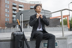 Mid adult businessman with luggage adjusting necktie against buildings Stock Photography