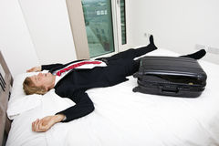 Mid adult businessman with luggage sleeping in bed at home Stock Photo