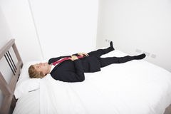 Mid adult businessman lying in bed at home Royalty Free Stock Image