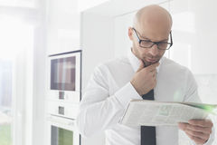 Mid adult businessman reading newspaper at home Royalty Free Stock Photos