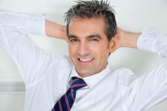 Mid Adult Businessman Relaxing With Hands Behind Stock Image