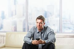 Businessman holding coffee mug on sofa Royalty Free Stock Photo