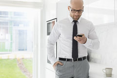 Mid adult businessman text messaging through smart phone at home Stock Image