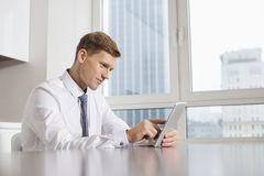 Mid adult businessman using digital tablet at kitchen table Stock Image