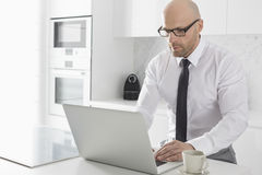 Mid adult businessman using laptop at kitchen counter Royalty Free Stock Image