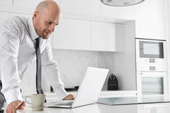 Mid adult businessman using laptop at kitchen counter Stock Photography
