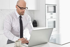 Mid adult businessman using laptop at kitchen counter Royalty Free Stock Photography