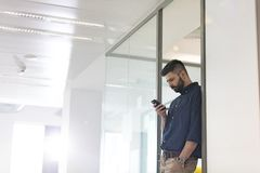 Mid adult businessman using mobile phone in office Stock Photo