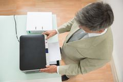 Mid-adult businessman using photocopy machine. High Angle View Of A Businessman Using Photocopy Machine In Office Royalty Free Stock Photos