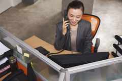 Mid adult businesswoman on the phone in the office Stock Photography