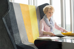 Mid adult businesswoman reading documents at desk in office Royalty Free Stock Photos
