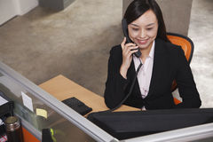 Mid adult businesswoman smiling and listening on the phone in the office Stock Photography