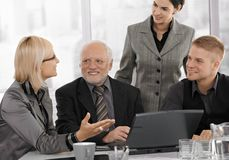 Mid-adult businesswoman talking to team royalty free stock photography